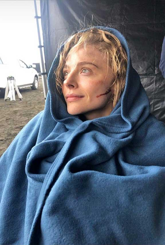 From soaked to snuggly: The actress bundles up in a blanket between takes.