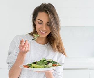 Brunette woman eating a salad