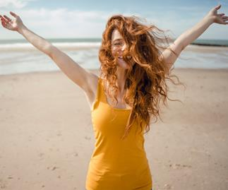 Redheaded woman, laughing happily in the wind