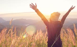 woman arms outstretched at sunrise