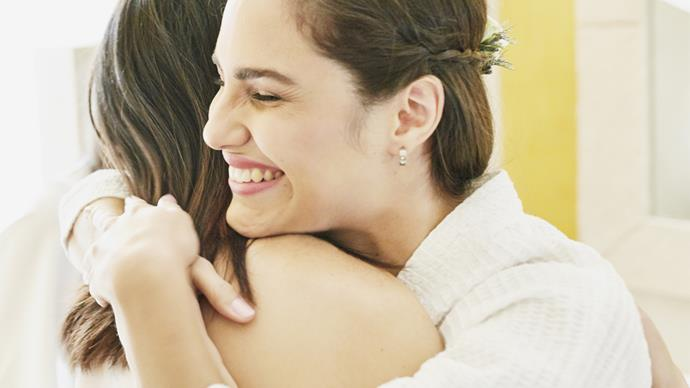Two brunette woman smiling hugging