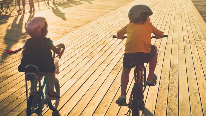 Family riding bikes along beach boardwalk