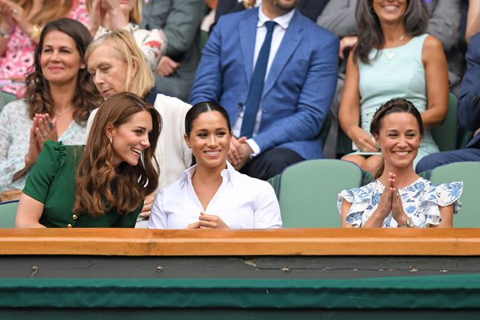 Meghan sat between the two Middleton sisters, with all of them chatting and laughing throughout the match. *(Image: Getty)*