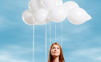 Red-headed woman looking up to sky white balloons forming clouds