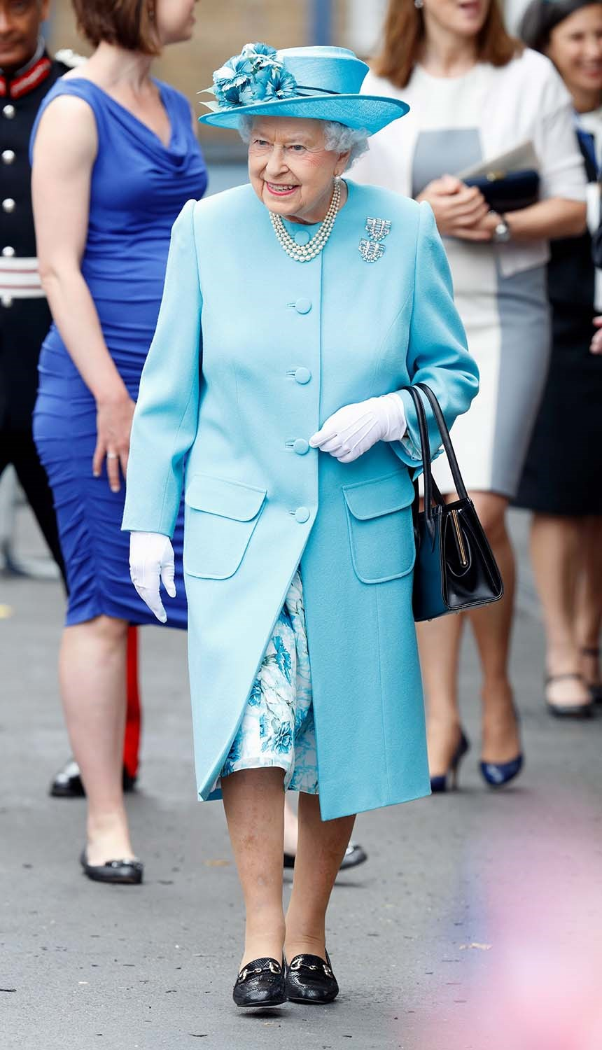 It's not often you'll see Her Majesty without her trademark Launer handbag. *(Image: Getty)*
