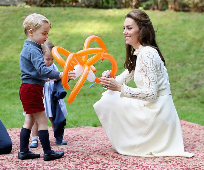 Prince George inspects a balloon during a visit to Canada. *(Image: Getty)*