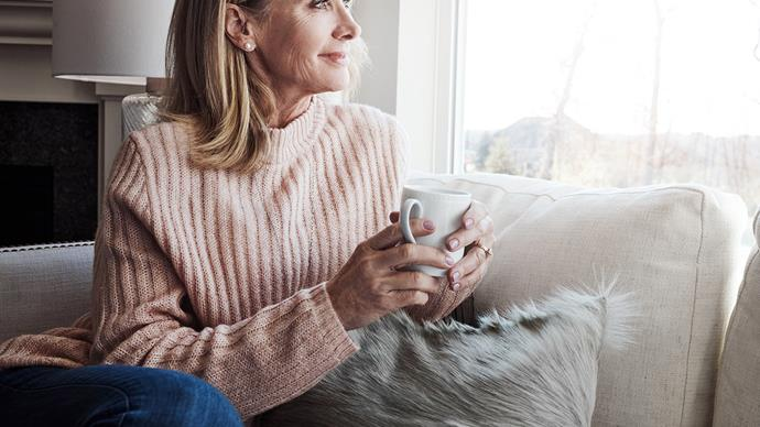 woman drinking tea looking out window