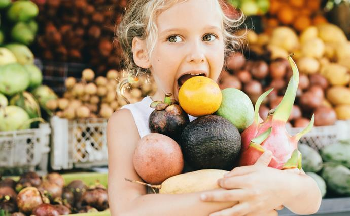 Young girl in market, arms full of produce