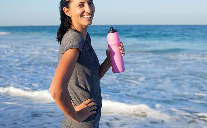 woman drinking from water bottle after exercise by the sea