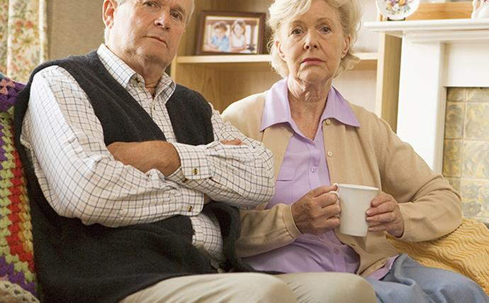 Unhappy couple sitting on sofa