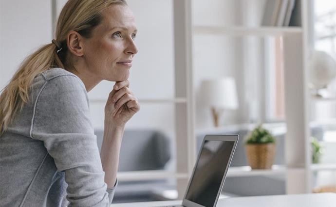 blonde woman sits at desk pensively relaxed