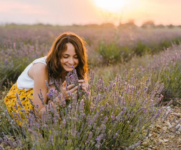 woman smelling lavender in field