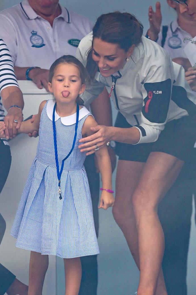 Cheeky Princess Charlotte playfully stuck out her tongue at the crowds below. *(Image: Getty)*