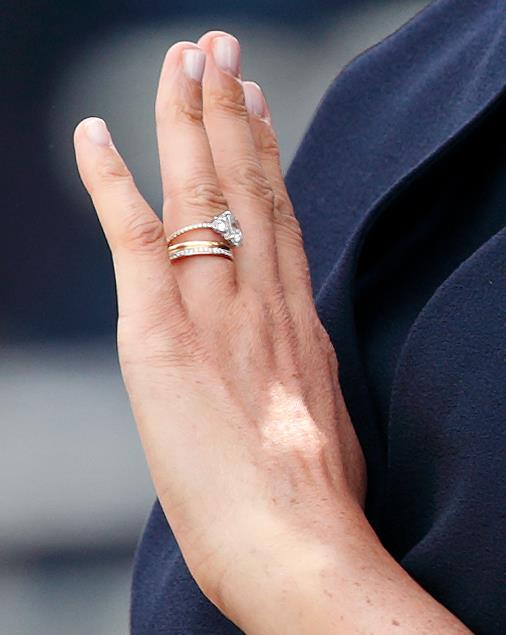 Meghan's three rings from top to bottom: her engagement ring, her wedding band, and her brand new eternity band. *(Image: Getty)*