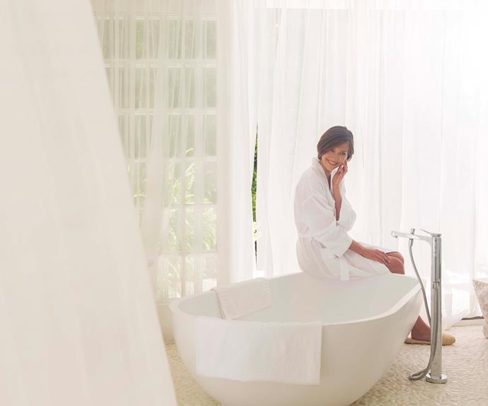 woman sitting by a bathtube in a bathrobe