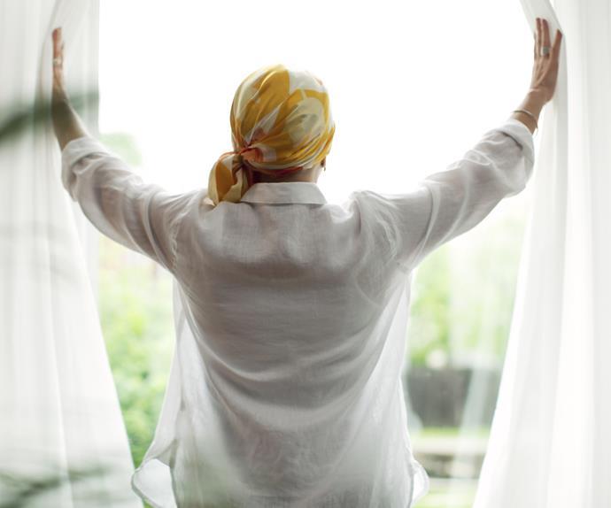 Woman wearing bandana opening curatins
