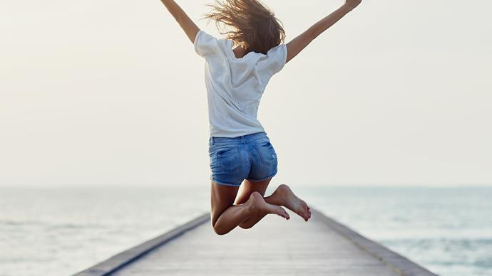 woman full of energy jumping on a pier