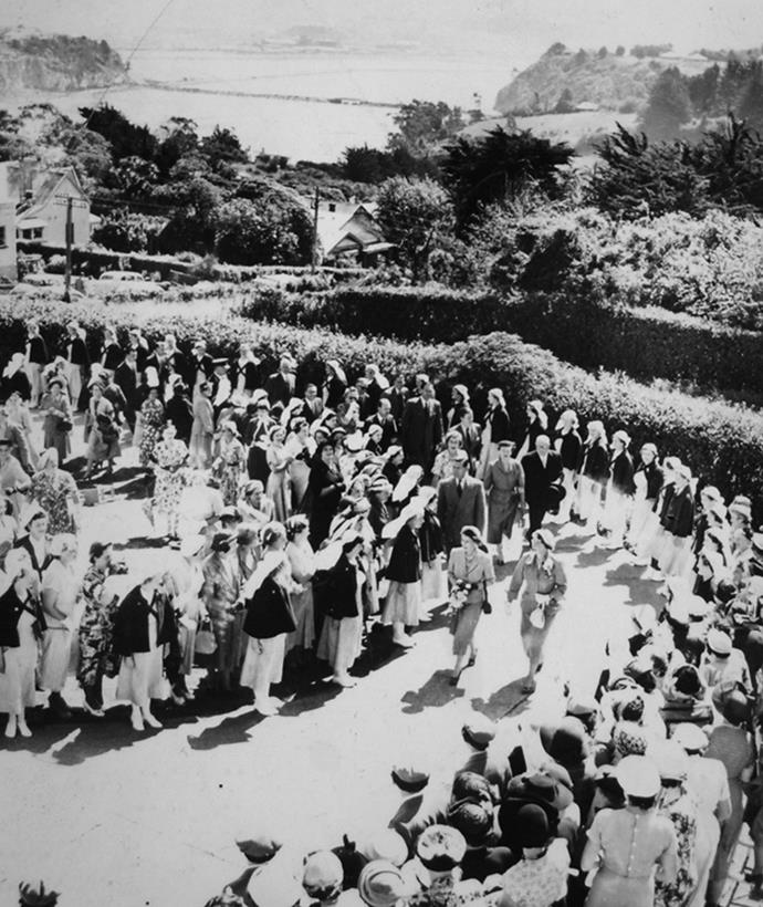 Nurses line the drive to the Karitane Hospital at Anderson's Bay, Dunedin, as the Queen arrives for a visit in 1954. Image: Getty Images