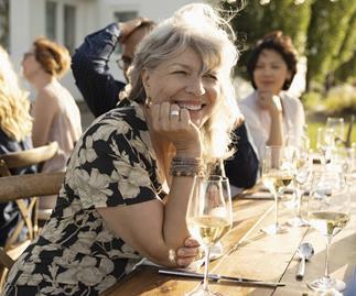 Smiling woman drinking wine at sunny garden party