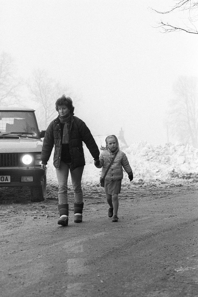 **Zara Phillips, 1987** <br><br> Princess Anne's second child, Zara, is wrapped up warm and cosy as she's led to her first day at Beaudsert Park School by her nanny. <br><br> *(Image: Getty)*