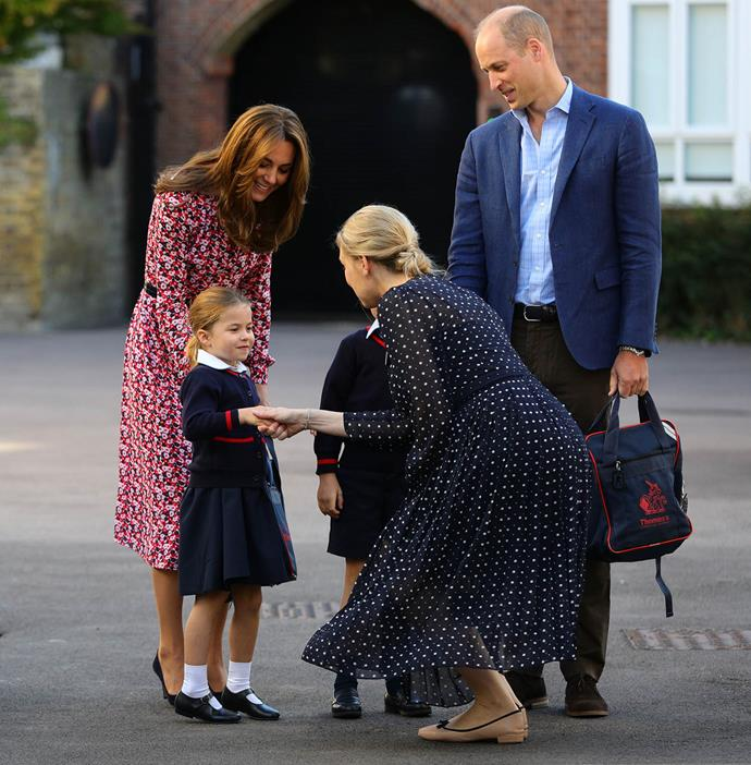 Charlotte looked much more relaxed as she shook hands with the head of the lower school, Helen Haslem. *(Image: Getty)*