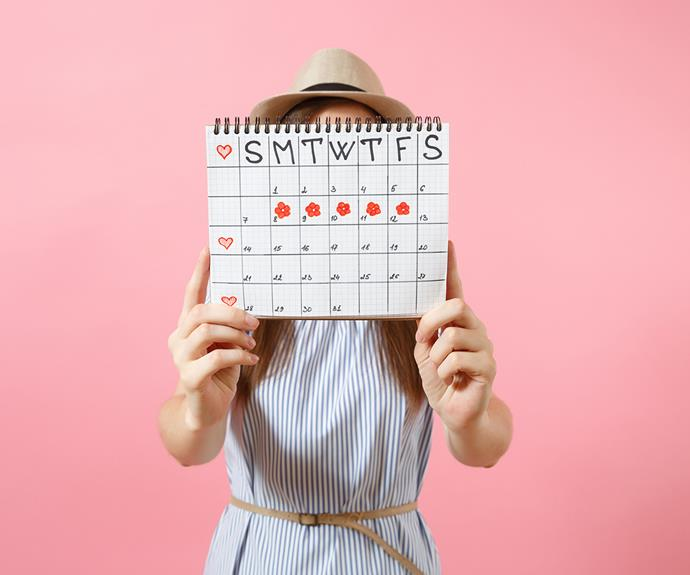 woman holding menstruation cycle chart