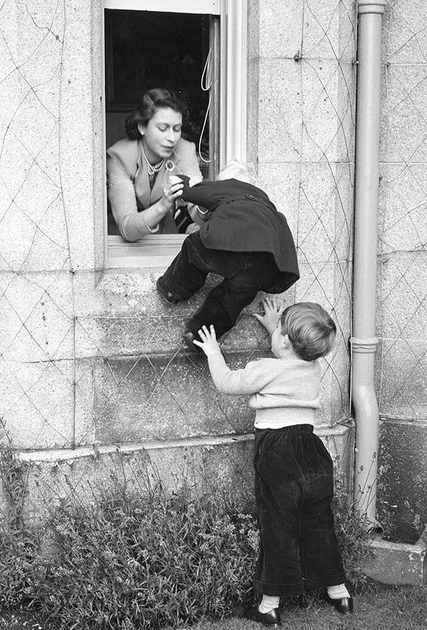 The then Duchess of York pulling Anne through a window with the help of a young Charles in 1952. Image: Getty