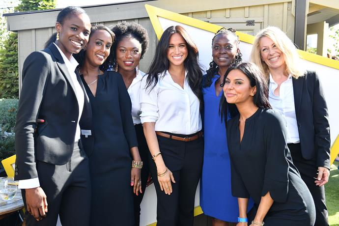 Meghan poses with women wearing items from the clothing collection. *(Image: Getty)*