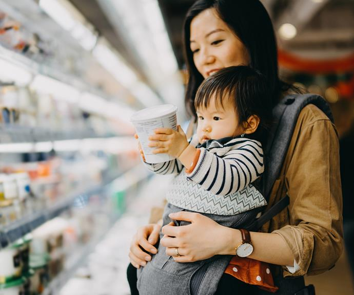 baby holding yoghurt tub in supermarket with mum