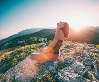 woman sitting on a mountain sun spot