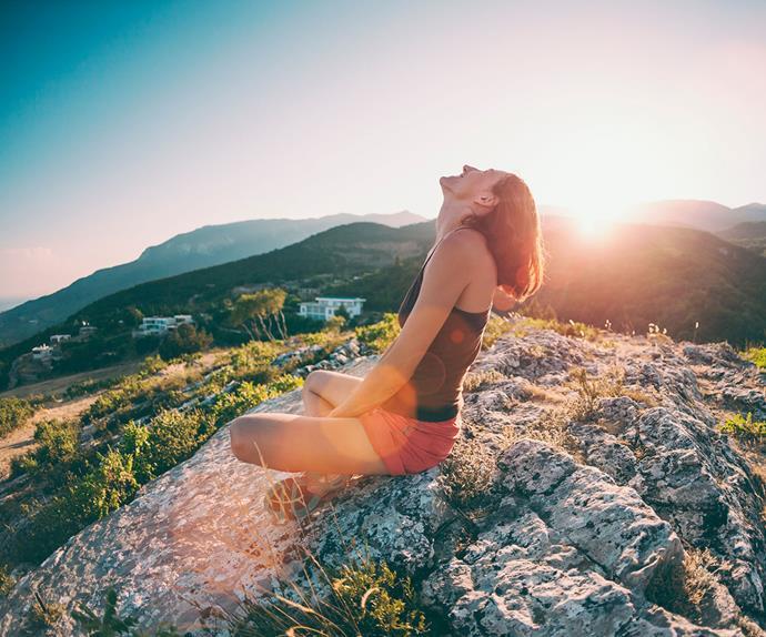woman sitting on a mountain sun spot