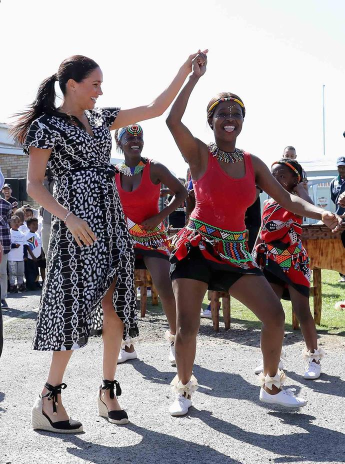 Meghan showed off her moves as she joined dancers for a boogie. *(Image: Getty)*