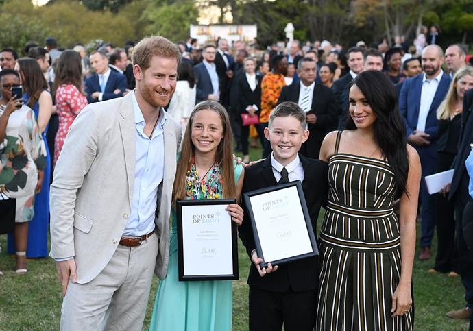 Harry and Meghan awarded young Jade and Hunter with Commonwealth Points of Lights awards for their incredible volunteer work. *(Image: Getty)*