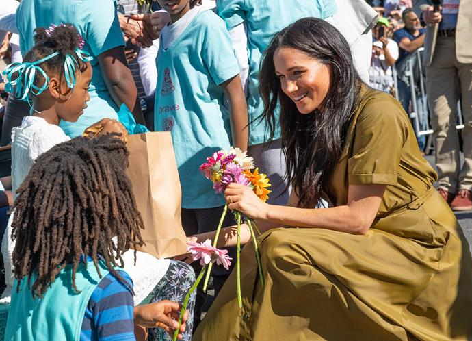 Meghan chatted with people from the Brave Foundation and walked away with an armful of gifts. *(Image: Getty)*