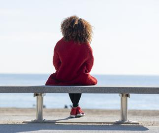 Rear view young woman sitting on a bench looking to horizon over sea