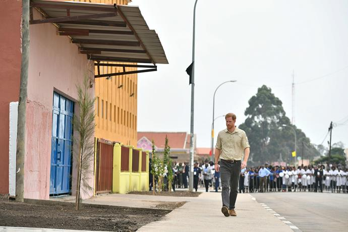 Prince Harry walks down a street in Huambo, which 22 years ago was the active de-mining zone which his mother was famously photographed in. *(Image: Getty)*