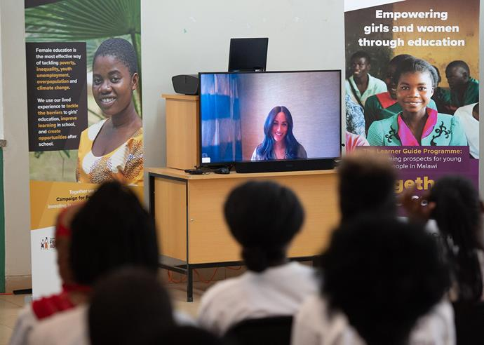 Meghan made a surprise appearance - via Skype - during Harry's visit to a school in Malawi. *(Image: Getty)*