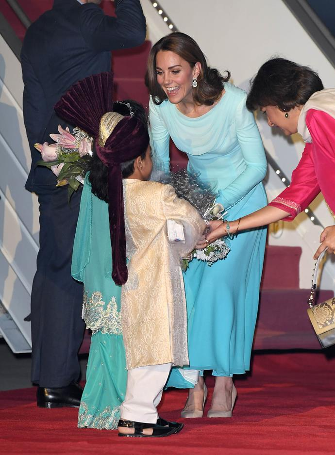Duchess Catherine is gifted a bouquet of flowers by two children as she arrives in Islamabad, Pakistan. *(Image: Getty)*