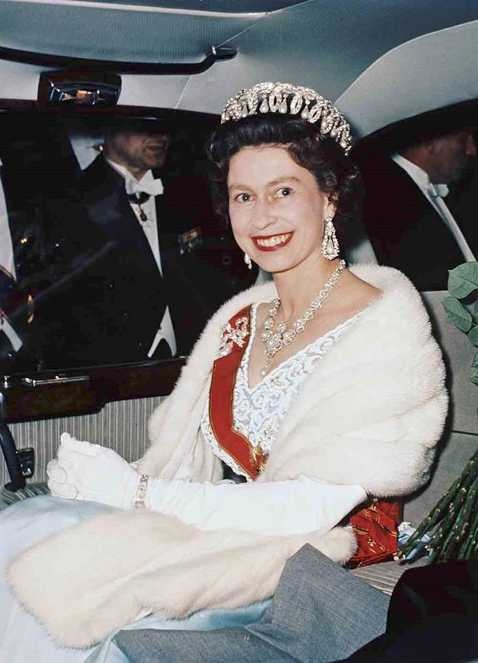 Queen Elizabeth wears a fur shawl during a visit to Bruhl, Germany in 1965. *(Image: Getty)*