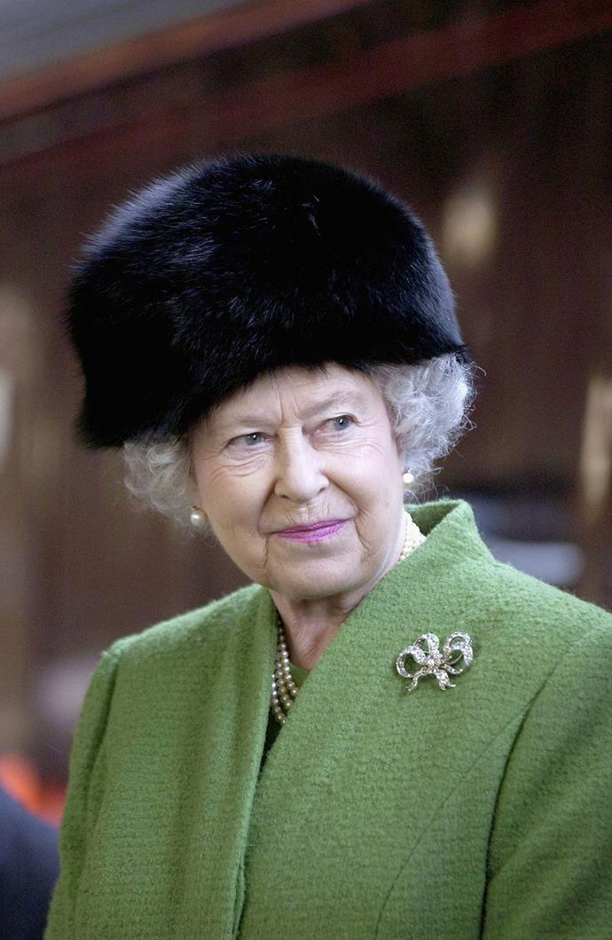 The Queen wears one of her many fur hats during a visit to Bristol, England in 2005. *(Image: Getty)*