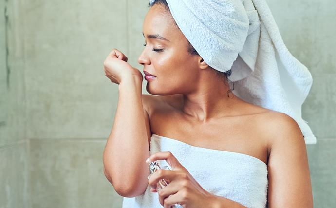 woman smelling wrist with perfume
