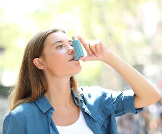 Asthmatic woman using inhaler standing in the street
