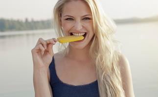 Smiling woman biting ice block