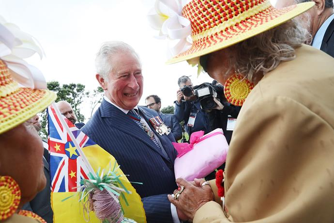 Despite the rain, Prince Charles was all smiles as he greeted the crowds. *(Image: Getty)*
