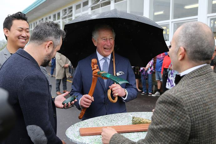 Prince Charles looks pretty chuffed with his Māori axe, made out of recycled plastic. *(Image: Getty)*