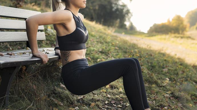 Woman working out on park bench tricep dip