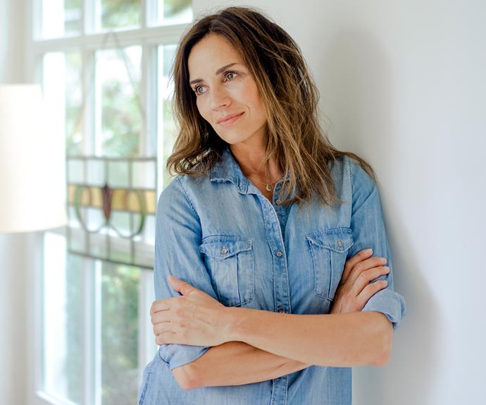 Mature woman leaning against wall deep in thought