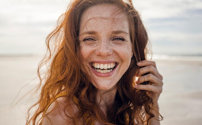 red headed woman smiling on a beach