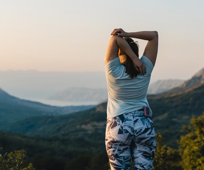 Woman with diabetes stretching on top of the hill