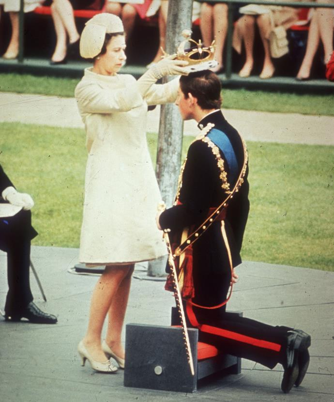 Her Majesty crowns Charles The Prince of Wales during his Investiture in 1969 - a title he has now held for 50 years. *(Image: Getty)*